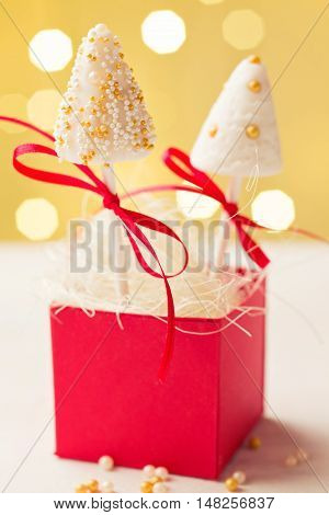 Cake pops made of fondant sticking in red gift box. Very shallow depth of field and Christmas lights in the background