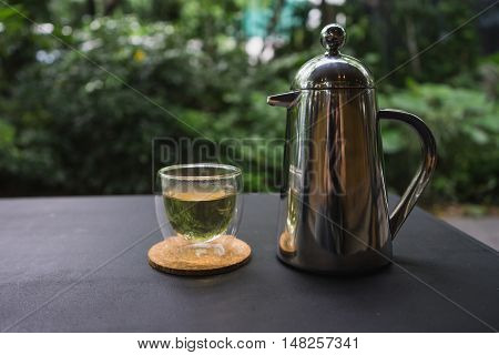 hot fresh tea in see through glass and silver shinning tea pot with silver spoon on black table at coffee time / hot fresh tea