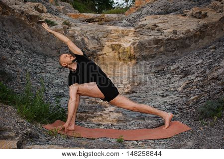 Sporty young man working out, yoga, pilates, fitness training, doing Utthita Trikonasana, Extended Triangle pose