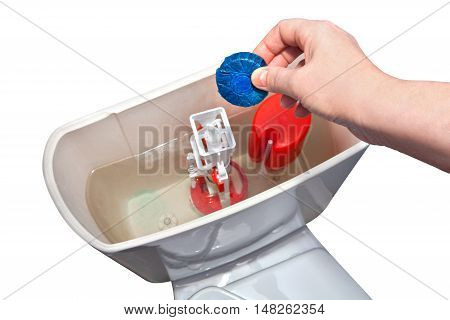 Hand holding a blue water-soluble tablet for cleaning the toilet bowl over the drain tank.