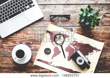 world map with laptop and coffee on wooden table time to travel top view