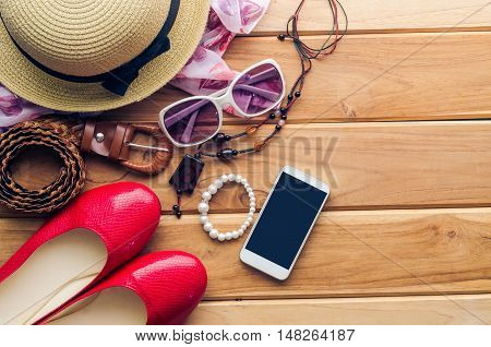 accessories for teenage girl on her vacation hat stylish for summer sun glasses leather bag shoes and costume on wooden floor.