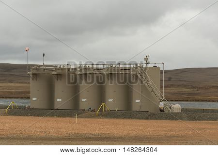 A group of oil storage tanks near a wetland in North Dakota