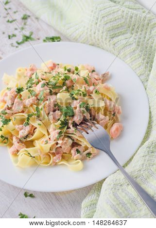 Italian Wholemeal Pasta Tagliatelle with Salmon and Parsley. Close up Fresh pasta with smoked salmon in the sauce on white wooden background. Italian cuisine concept. Selective focus.