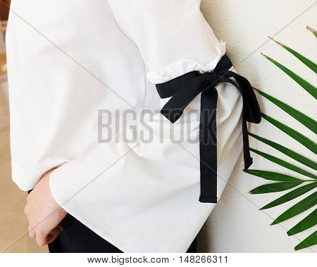 long white sleeve with black string bow tie style details. Close up trendy fashion.