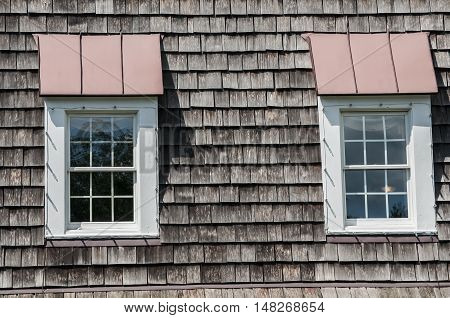 Two attic windows of pointed wooden roof of old house