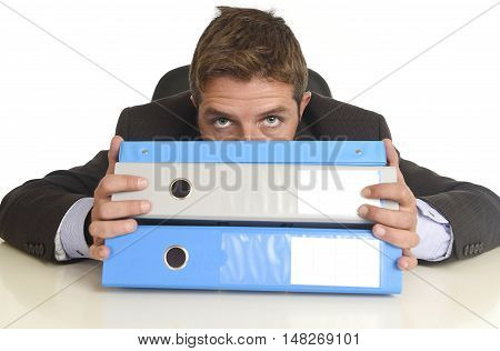 young attractive busy businessman overwhelmed suffering stress at office exhausted and helpless hiding behind paperwork folders pile on desk in business frustration and overwork problem