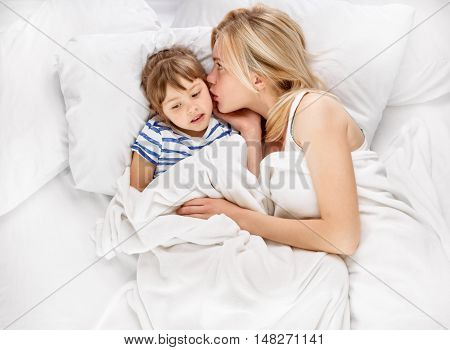 whispering joyful mother and her little daughter in the bed, shot from above