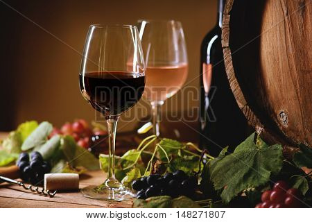 Wine bottle, glasses, grapes and barrel on a table