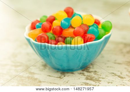 Bowl filled with jelly beans colors on a wooden table