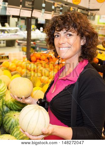 Smiling Woman Shopping In Supermarket Department Of Fruits