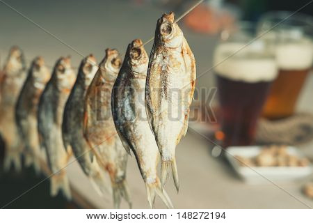 Dried fish on a beer glasses background