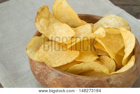 Delicious crispy potato chips in an old wooden bowl.