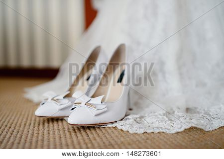 Beautiful White Wedding Dress And Shoes For Bride Indoors. Beauty Of Bridal Gown For Marriage. Femal