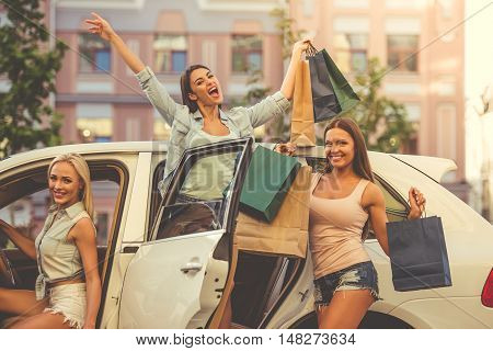 Beautiful stylish girls are holding shopping bags looking at camera and smiling while standing near their car outdoors