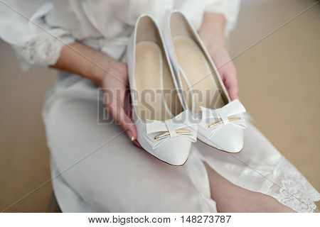 Beautiful Bride In White Wedding Dress Is Holding Shoes In Her Hands. Beauty Model Girl In Bridal Go