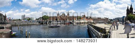 AMSTERDAM - JULY 10 2016: Big panoramic of Central Station and canal July 10 2016 in Amsterdam. Central Station is the central railway station of Amsterdam and is used by 250000 passengers a day.