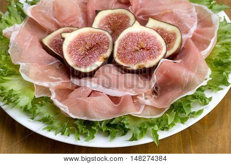 Prosciutto Served With Figs On Lettuce Leaves