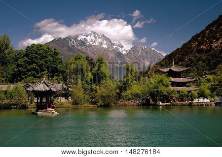 Lijiang China - April 19 2006: Small pagodas and crystal clear waters in Black Dragon Pool Park with Jade Dragon Snow Mountain in the distance