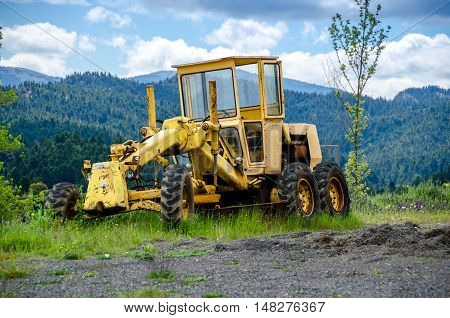 A old yellow grader on mountainous road construction