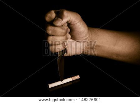 Handle knife stabbed into cigarettes concept eliminate smoking quit smoking.