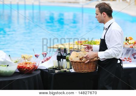young people serving food on buffet wedding seminar or conference outdoor party with fresh food and drink