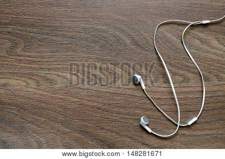White stereo earphones on wooden board, copyspace