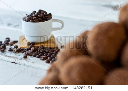 White cup with coffee beans. Dark grains on wooden surface. Caffeine boosts energy. Basic ingredient for delicious drink.