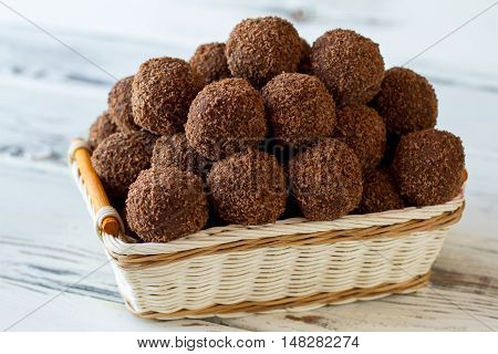 Brown sweets in a basket. Small desserts with crumbs. Chocolate balls cooked at home. Butter and cocoa powder.