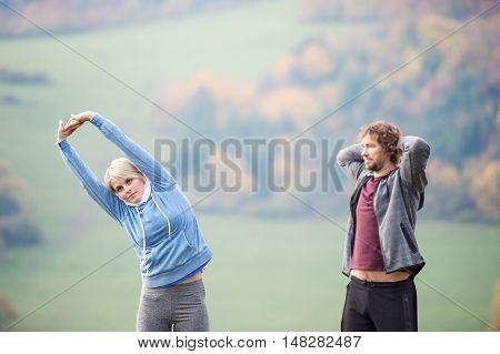 Two young beautiful runners in colorful autumn nature, stretching arms