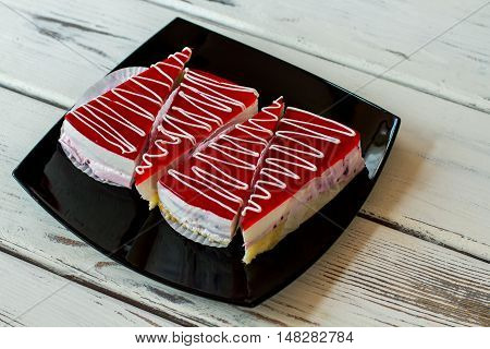 Four slices of cake. Dessert on black plate. Mousse and jelly. Appetizing sweet dish in cafeteria.