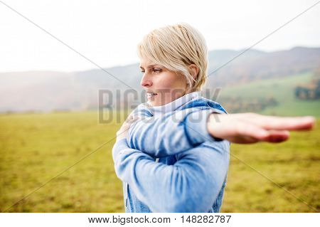 Young blond runner outside in sunny nature, stretching her arm