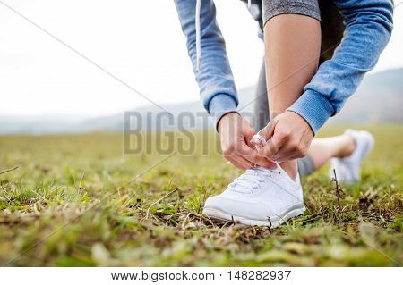 Close up of an unrecognizable young runner tying shoelaces, autumn nature