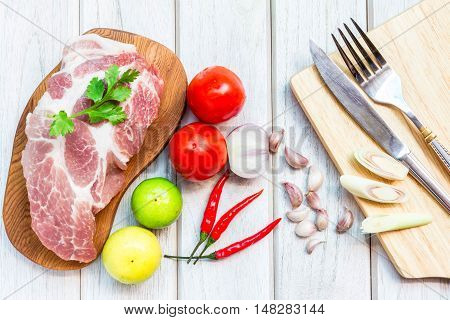 culinary background with spices and pork on wooden table