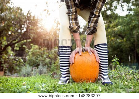 Unrecognizable woman in striped rubber boots and checked shirt holding orange pumpkins. Sunny autumn nature.