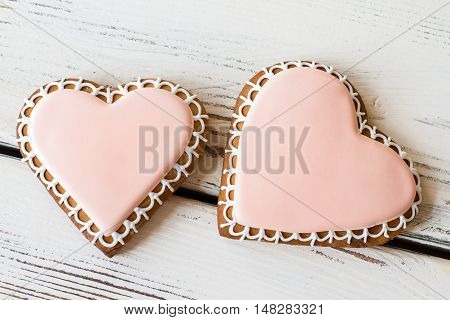 Two heart-shaped cookies. Biscuits on white wooden background. Small romantic present. Flavor of happiness.