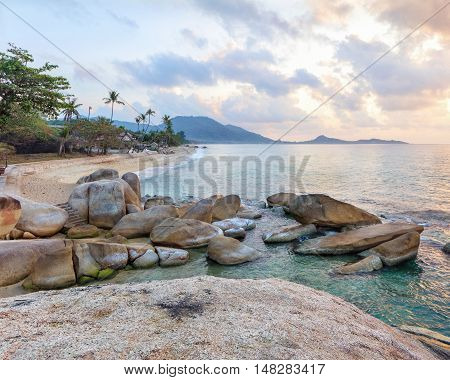 Empty morning Samui beach with beach rocks on foreground