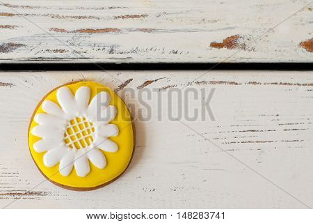 Cookie with picture of flower. Yellow and white icing. Beauty of plain things. Tasty biscuit with glaze.