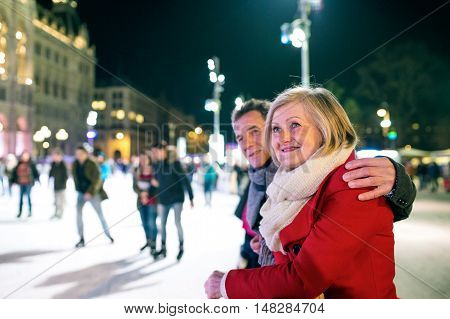 Beautiful senior couple ice skating at night in historical centre of the city of Vienna, Austria. Winter.
