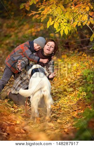Happy mom and her son with golden retriever in autumn park