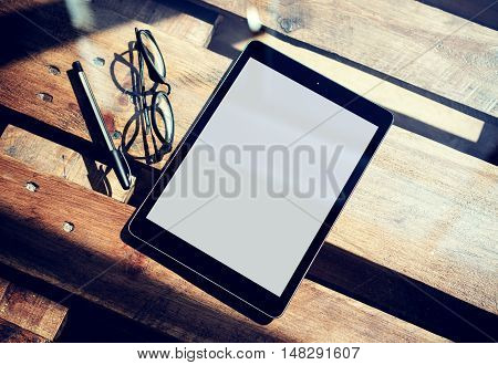 Closeup Modern Tablet White Blank Screen Gadget and Classic Glasses Wood Table Inside Interior Coworking Studio Place.Reflections Natural Background. Blurred Horizontal