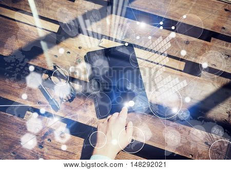 Global Interfaces Virtual Graph Icon Innovation.Concept Mans Hand Touching Home Button Modern Tablet.Black Screen Gadget and Glasses Wood Table Inside Interior Coworking Studio Place. Horizontal