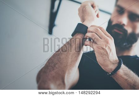 Close-up Shot Young Bearded Sportive Man After Workout Session Checks Fitness Results Smart Watch.Adult Guy Athlete Wearing Sport Tracker.Training hard gym.Horizontal bar background.Blurred