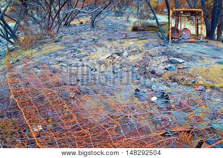 Remnants of a home including a burnt mattress foundation and other objects taken after a fire