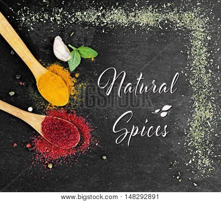 Composition of different spices on dark background. Text Natural Spices.