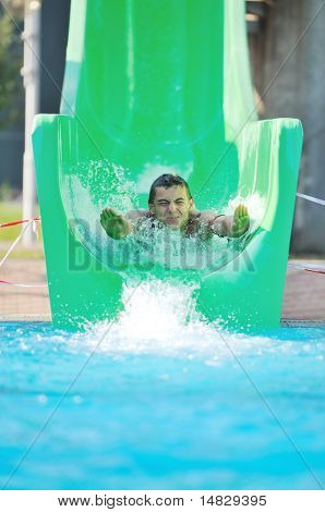 happy girl have fun  on water slide at outdoor swimming pool