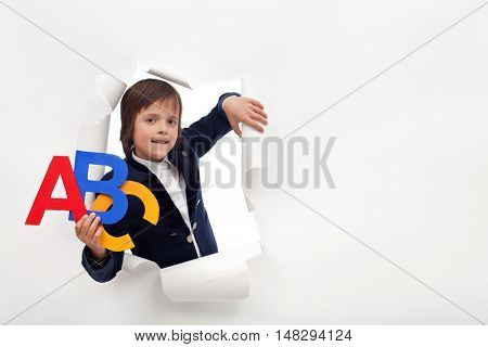 Time to learn - young school boy with colorful alphabet letters leaning through hole in paper layer