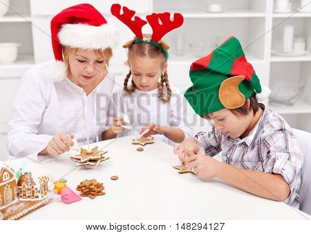 Helping mom with the christmas cookies - woman and kids decorating home made biscuits