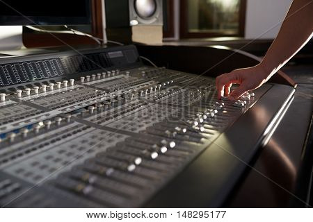 Hands of professional musician using mixer in studio