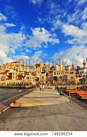 TEL AVIV, ISRAEL - NOVEMBER 22, 2014: Sunny day. People walk on the promenade on warm autumn day. The ancient port of Old Jaffa